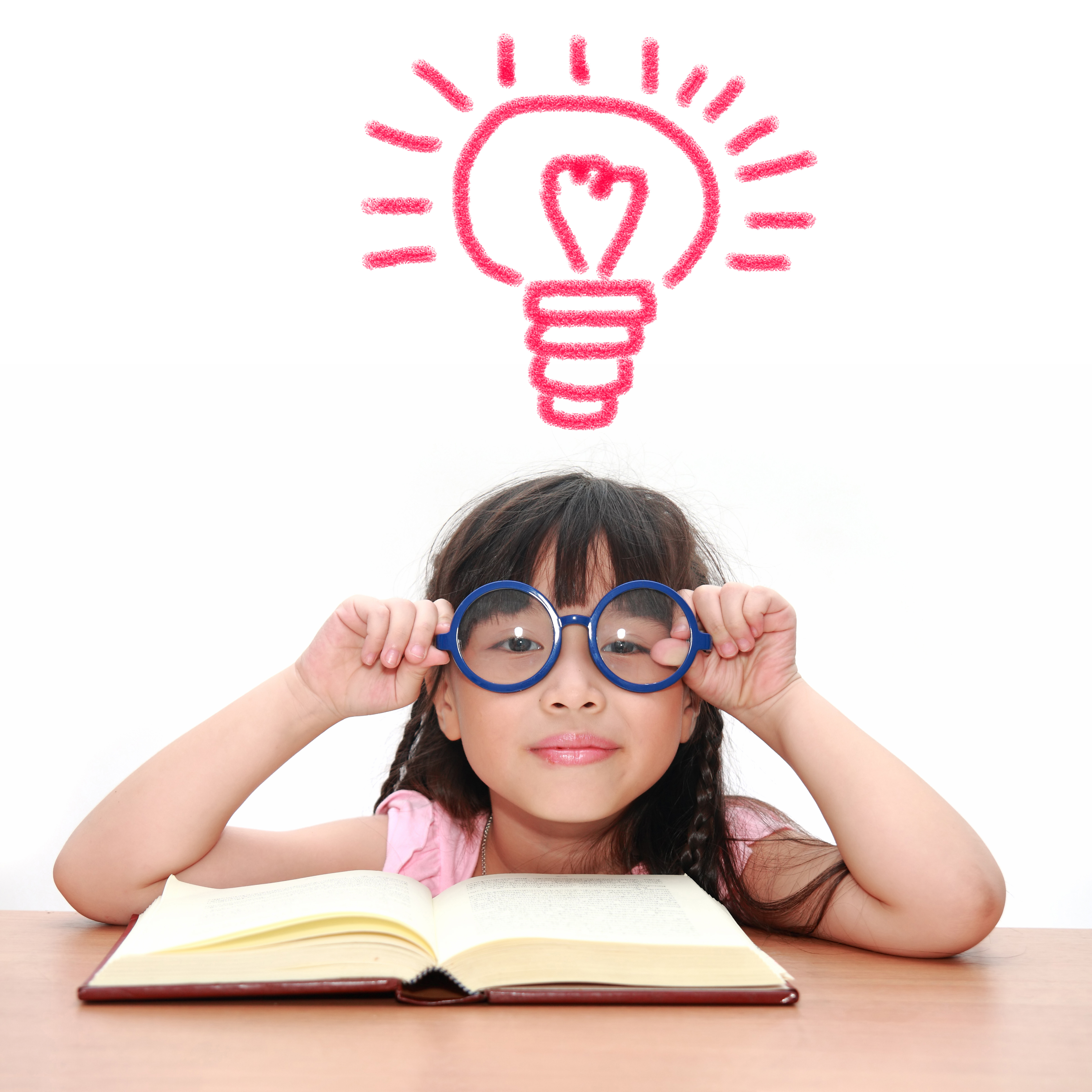 A girl with glasses reading a book with a drawn lighbulb over her head